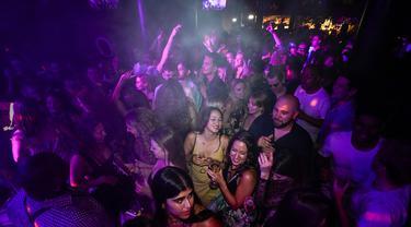 Orang-orang minum di lantai dansa tak lama setelah pembukaan kembali, di The Piano Works di Farringdon, London, Senin (19/7/2021). Ribuan anak muda berdansa semalaman di pesta 'Hari Kebebasan', ketika hampir semua pembatasan virus corona di Inggris dibatalkan. (AP Photo/Alberto Pezzali)