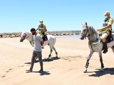 Sejumlah tentara berkuda yang berpatroli di sebuah pantai mengawal seorang pria agar meninggalkan lokasi tersebut di Sale, Maroko, Minggu (14/6/2020). Maroko pada 14 Juni 2020 mengumumkan 101 infeksi baru COVID-19, menambah jumlah kasus terkonfirmasi di negara tersebut menjadi 8.793. (Xinhua/Chadi)