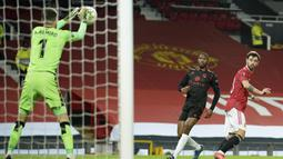 Kiper Real Sociedad, Alex Remiro berhasil menangkap bola tendangan gelandang Manchester United, Bruno Fernandes (kanan) dalam laga leg kedua babak 32 Besar Liga Europa 2020/21 di Old Trafford Stadium, Kamis (25/2/2021). Real Sociedad bermain imbang 0-0 dengan Manchester United. (AP/Dave Thompson)