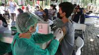 Vaksinator menyuntikkan vaksin COVID-19 untuk warga di Taman Dadap Merah, Kebagusan, Jakarta, Sabtu (10/7/2021).  Pelaksanaan vaksinasi melalui mobil vaksin keliling juga diperuntukkan untuk anak usia 12 tahun ke atas. (Liputan6.com/Helmi Fithriansyah)