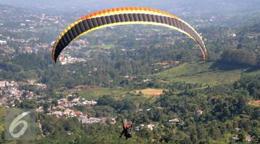 Olahraga Paralayang menjadi pilihan warga yang berkunjung ke Puncak Pass, Bogor, Jumat (6/4). Olahraga yang memacu adrenalin ini dipatok dengan harga Rp. 350 Ribu. (Liputan6.com/Johan Tallo)