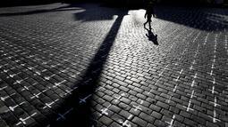 Seorang perempuan melintasi Alun-alun Kota Tua di Praha di mana ribuan salib dilukis untuk menandai satu tahun sejak kematian pertama akibat Covid-19 di Republik Ceko, Senin (22/3/2021). Sekelompok aktivis melukis salib untuk mengkritik tanggapan pemerintah terhadap pandemi. (AP/Petr David Josek)
