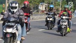 Pemudik sepeda motor dengan membawa anak melintasi Jalur Pantura Cirebon, Jawa Barat, Kamis, (29/6). Memasuki H+4 Lebaran jalur Pantura Cirebon mengarah ke Jakarta mulai dipadati pemudik pengguna kendaraan bermotor roda dua (Liputan6.com/Helmi Afandi)