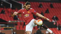 Striker Manchester United, Edinson Cavani melepaskan tendangan voli yang berbuah gol pertama timnya ke gawang Granada dalam laga leg kedua perempatfinal Liga Europa 2020/2021 di Old Trafford Stadium, Manchester, Kamis (15/4/2021). Manchester United menang 2-0 atas Granada. (AFP/Oli Scarff)