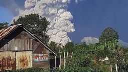 Gunung Sinabung menyemburkan abu ke langit, terlihat dari Karo, Sumatera Utara, Selasa (2/3/2021).   Guguran awan panas tersebut meluncur ke arah timur tenggara dengan jarak luncur 3 kilometer. (AFP/Bahari Tarigan)