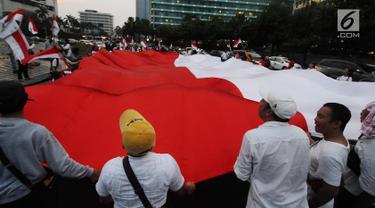 Sejumlah pendukung capres-cawapres 01 Jokowi-Ma'ruf Amin membentangkan bendera merah putih di kawasan bunderan HI, Jakarta, Rabu (17/4). Pendukung capres-cawapres 01 arak-arakan merayakan unggul dalam versi hitungan cepat. (Liputan6.com/Herman Zakharia)