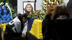 Keluarga duduk disamping peti jenazah korban yang tewas dalam insiden jatuhnya pesawat Ukraine International Airlines di Iran (8/1) lalu, Bandara Boryspil Kiev, Ukraina, Minggu (19/1/2020). Pesawat tersebut jatuh oleh rudal pasukan IRGC. (Ukrainian Presidential Press Service/AFP)