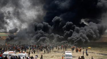 Kepulan asap hitam membubung di pagar perbatasan Palestina-Israel di kota Gaza tengah (13/4). Ratusan warga Palestina membakar ban saat melakukan unjuk rasa di perbatasan Palestina-Israel. (AFP/Mohammed Abed)