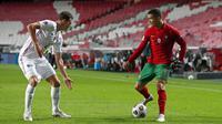 Striker Portugal, Cristiano Ronaldo, berusaha melewati bek Prancis, Benjamin Pavard, pada laga UEFA Nations League di Stadion Da Luz, Minggu (15/11/2020). Prancis menang dengan skor 1-0. (AP/Armando Franca)
