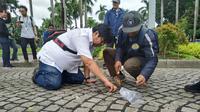 Tim asistensi Komisi Pengarah (komrah) kawasan Medan Merdeka mengambil sampel aspal yang diperuntukan lintasan Formula E, Rabu (26/2/2020). (Merdeka.com/ Yunita Amalia)