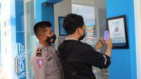 Pemohon SIM ketika menscan barcode aplikasi Peduli Lindungi di pintu keluar masuk Satpas Polres Blora. (Liputan6.com/Ahmad Adirin)