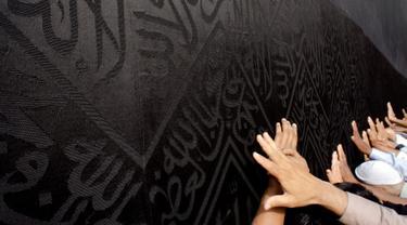 Umat muslim memanjatkan doa dengan menyentuh dinding Kabah selama menjalani ibadah umrah di Masjidil Haram, Mekkah, 4 Mei 2018. Banyak umat muslim yang menyambut bulan Ramadan dengan menjalankan ibadah umrah ke tanah suci. (AP Photo/Amr Nabil)