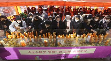 Para orangtua meletakkan lilin selama kebaktian khusus untuk mendoakan keberhasilan anak-anak mereka dalam ujian masuk perguruan tinggi di Kuil Buddha Jogyesa, Seoul, Korea Selatan, Kamis (3/12/2020). Ujian diikuti ratusan ribu siswa, termasuk puluhan siswa pasien COVID-19. (AP Photo/Ahn Young-joon)