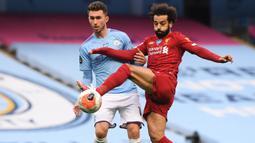 Penyerang Liverpool, Mohamed Salah, berebut bola dengan bek Manchester City, Aymeric Laporte, pada laga lanjutan Premier League pekan ke-32 di Stadion Etihad, Jumat (3/7/2020) dini hari WIB. Manchester City menang 4-0 atas Liverpool. (AFP/Laurence Griffiths/pool)