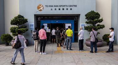 Sejumlah orang menunggu dalam antrean di pusat pengujian virus corona COVID-19, Hong Kong, Selasa (1/9/2020). Hong Kong mulai melakukan tes massal virus corona COVID-19. (ISAAC LAWRENCE/AFP)