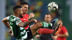 Gelandang Sporting Lisbon, Rafael Camacho (kiri) berebut bola dengan gelandang Benfica, Julian Weigl dalam laga lanjutan Liga Portugal 2020/21 di Jose Avalade Stadium, Lisbon, Senin (1/2/20201). Sporting menang 1-0 atas Benfica. (AFP/Patricia De Melo Moreira)
