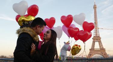 Gerson asal Honduras melamar pasangannya Andry pada Hari Valentine ketika berdiri di Trocadero Plaza dekat Menara Eiffel di Paris, Prancis (14/2). (AFP Photo/Ludovic Marin)
