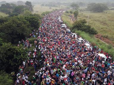 Rombongan imigran Amerika Tengah tujuan Amerika Serikat berkumpul di jalan raya setelah polisi federal memblokir jalan mereka di luar Kota Arriaga, Meksiko, Sabtu (27/10). Pemerintah Meksiko menghalangi rombongan menuju AS. (AP Photo/Rodrigo Abd)