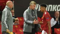 Pelatih Manchester United, Ole Gunnar Solskjaer, berbincang dengan Jesse Lingard pada laga leg kedua 16 besar Liga Europa 2019/2020 di Old Trafford, Kamis (6/8/2020) dini hari WIB. Manchester United menang agregat 7-1 atas LASK. (AFP/Oli Scarff)