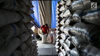 Pekerja mamasukan beras ke dalam karung di Pasar Induk Beras Cipinang, Jakarta Timur, Kamis (24/8). Sementara untuk wilayah lainnya yang membutuhkan ongkos transportasi lebih harga tersebut ditambah Rp 500 per kg. (Liputan6.com/Johan Tallo)