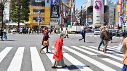 Pejalan kaki melintasi persimpangan pejalan kaki yang terkenal di distrik Shibuya, Tokyo pada 20 Maret 2019. Persimpangan jalan ini menjadi salah satu persimpangan terbesar dan tersibuk di dunia. (Photo by CHARLY TRIBALLEAU / AFP)