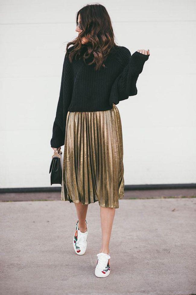Buat penampilan kamu terlihat unik dan berbeda dengan memakai black sweater and gold pleated skirt, lalu pakai sneakers putih. (sumber foto: hellofashionblog.com/pinterest)