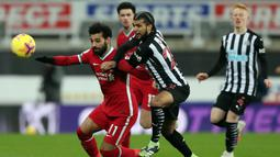 Gelandang Liverpool, Mohamed Salah (kiri) berebut bola dengan bek Newcastle United, DeAndre Yedlin dalam laga lanjutan Liga Inggris 2020/21 pekan ke-16 di St James' Park, Rabu (30/12/2020). Liverpool bermain imbang 0-0 dengan Newcastle United. (AFP/Scott Heppell/Pool)