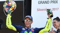 Momen saat pembalap Movistar Yamaha, Valentino Rossi naik podium ketiga MotoGP Inggris 2017 di Sirkuit Silverstone, Minggu (27/8/2017). (AP Photo/Rui Vieira)