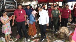 Presiden Joko Widodo atau Jokowi menyalami warga saat blusukan di Pasar Minggu, Jakarta, Jumat (22/2). Jokowi mengenakan kemeja putih lengan panjang, celana hitam, dan sepatu sneakers. (Liputan6.com/Angga Yuniar)