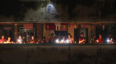 Warga menyalakan lilin dan obor untuk menandai perjuangan melawan pandemi virus corona COVID-19 di Mumbai, India, Minggu (5/4/2020). Perdana Menteri India Narendra Modi mengimbau warga mematikan lampu untuk menunjukkan dukungan mereka terhahap perjuangan melawan COVID-19. (AP Photo/Rafiq Maqbool)