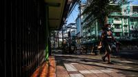 Pejalan kaki melintas di depan pertokoan yang tutp saat PPKM Level 4 di Jakarta, Minggu (1/8/2021). Sebelumnya bisa mencapai angka 350 - 400 kematian per hari. (Liputan6.com/Johan Tallo)