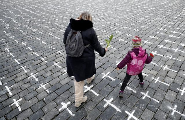 Seorang ibu dan anak membawa bunga saat ribuan salib dilukis di Alun-alun Kota Tua untuk memperingati setahun kematian pasien pertama COVID-19 Ceko, di Praha, Senin (22/3/2021). Pria 95 tahun adalah orang pertama yang meninggal pada 22 Maret 2020 di rumah sakit Bulovka Praha. (AP/Petr David Josek)