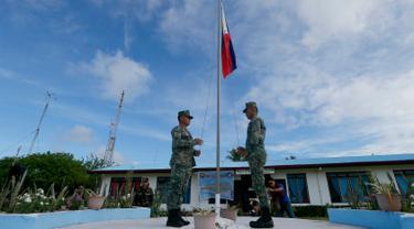 Tentara Filipina menaikan bendera saat mengikuti upacara di Pulau Thitu, Kepulauan Spratly, Laut China Selatan, Jumat (21/4). Pengibaran bendera Filipina yang sebelumnya dibatalkan  Presiden Duterte  akhirnya dilaksanakan. (AP Photo / Bullit Marquez)