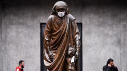 Masker terpasang pada wajah patung Bunda Teresa di Pristina, Kosovo, Kamis (19/12/2019). Selama beberapa bulan terakhir, Pristina terdaftar sebagai salah satu kota dengan kualitas udara terburuk di dunia. (Armend NIMANI/AFP)