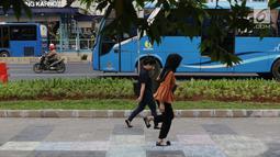 Pejalan kaki bermain permainan anak engkle di trotoar sekitar Halte Gelora Bung Karno, Jakarta, Jumat (17/5/2019). Koalisi Pejalan Kaki melakukan eksperimen permainan untuk mengedukasi kegiatan mengembalikan fungsi trotoar lebih dari sekedar ruang berjalan kaki. (Liputan6.com/Helmi Fithriansyah)
