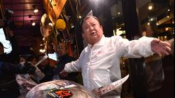 Pengusaha restoran sushi Jepang, Kiyoshi Kimura memamerkan ikan tuna sirip biru seberat 276 kg di restoran utamanya di Tokyo, Minggu (5/1/2020). Tuna raksasa itu dibeli mencapai Rp 24 miliar dan disebut sebagai yang tertinggi kedua dalam rekor lelang ikan di Pasar ikan Toyosu. (Kazuhiro NOGI / AFP)