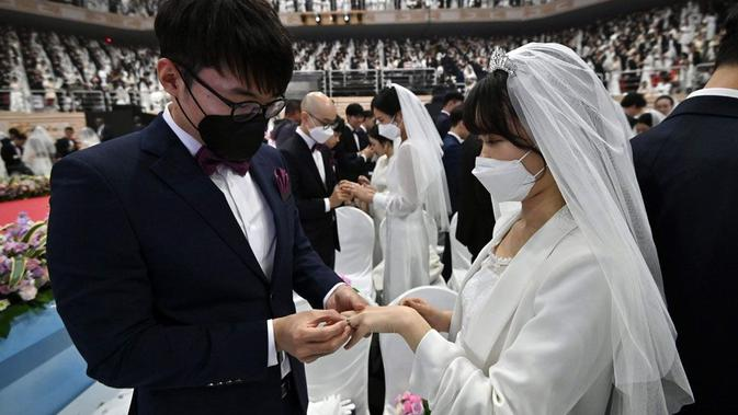 Peserta pernikahan massal di Korea Selatan terpaksa mengenakan masker guna mengantisipasi penyebaran Virus Corona. (Source: AFP)
