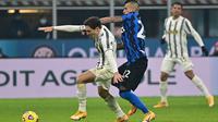 Gelandang Juventus, Federico Chiesa membaw bola dari kawalan gelandang Inter Milan, Arturo Vidal  pada pertandingan lanjutan Liga Serie A Italia di stadion San Siro di Milan, Senin (18/1/2021). Inter menang atas Juventus 2-0. (AFP/Miguel Medina)