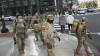 Anggota Garda Nasional menyeberang jalan di Washington, DC, saat pengamanan diperketat pada Senin (18/1/2021). Menurut laporan, 25.000 tentara Garda Nasional akan menjaga kota tersebut sebagai persiapan untuk pelantikan Joe Biden sebagai Presiden ke-46 Amerika Serikat. (Brendan Smialowski/AFP)