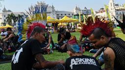 Anak-anak punk berbincang saat berpartisipasi merayakan festival air di pasar Bogyoke, Yangon, Jumat (12/4). Anak-anak punks ini berkumpul untuk menyambut dan merayakan festival air Tahun Baru Myanmar yang juga dikenal sebagai Thingyan. (AFP Photo/ Ye Aung Thu)