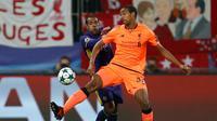 Pemain Liverpool, Joel Matip berebut bola dengan pemain Maribor, Marcos Tavares dalam lanjutan fase Grup E Liga Champions di Stadion Ljudski Maribor, Selasa (17/10). The Reds memetik kemenangan telak dengan skor meyakinkan 7-0. (AP/Darko Bandic)