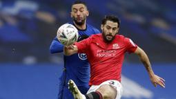 Pemain Chelsea, Hakim Ziyech, berebut bola dengan pemain Morecambe, Stephen Hendrie, pada laga Piala FA di Stadion Stamford Bridge, Minggu (10/1/2021). Chelsea menang dengan skor 4-0. (AP/Matt Dunham)