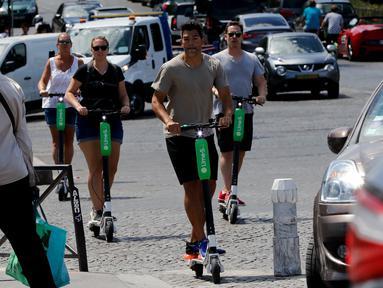 Orang-orang beraktivitas menggunakan skuter listrik di Paris, Prancis (9/7). Skuter listrik ini dibuat oleh perusahaan AS Lime yang merupakan penyewaan transportasi sepeda dan skuter di berbagai kota. (AFP Photo/Francois Guillot)