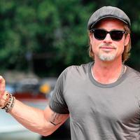 Aktor Brad Pitt berpose saat tiba di Pantai Lido untuk menghadiri Venice Film Festival 2019, Venesia, Italia, Rabu (28/8/2019). Brad Pitt tampak santai dengan mengenakan celana jeans hitam, kaus oblong, kaca mata hitam, dan topi newsboy cap. (Ettore Ferrari/ANSA via AP)