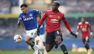 Gelandang Manchester United, Paul Pogba, berebut bola dengan gelandang Everton, Allan, pada laga lanjutan Liga Inggris di Goodison Park Stadium, Sabtu (7/11/2020) malam WIB. Manchester United menang 3-1 atas Everton. (Clive Brunskill/Pool via AP)