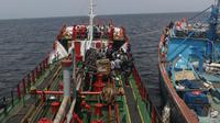 Dua kapal berjenis motor tanker dan kapal ikan yang diamankan petugas Badan Keamanan Laut (Bakamla) RI di perairan Teluk Jakarta, Jumat (1/2). Kapal tanker itu diduga telah melakukan transfer BBM ke kapal ikan sekitar 41 ton. (Liputan6.com/Angga Yuniar)