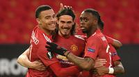 Striker Manchester United, Edinson Cavani (tengah) bersama rekan setim merayakan gol pertama yang dicetaknya ke gawang Granada dalam laga leg kedua perempatfinal Liga Europa 2020/2021 di Old Trafford Stadium, Manchester, Kamis (15/4/2021). Manchester United menang 2-0 atas Granada. (AFP/Oli Scarff)
