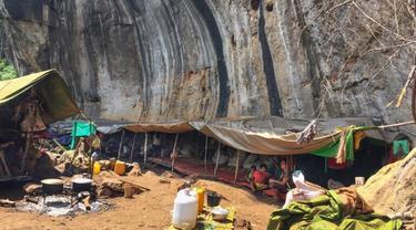 Foto ini diambil pada 1 Juni 2021 menunjukkan orang-orang berlindung di kawasan hutan di Demoso, negara bagian Kayah, setelah mereka melarikan diri dari pertempuran antara militer Myanmar dan anggota Tentara Pertahanan Rakyat (PDF) [Stringer/ AFP]