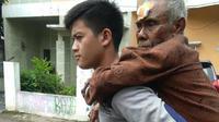 Petugas menggendong lansia tersebut saat mengantarkan ke rumahnya. (Istimewa)