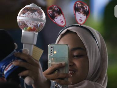 Penggemar berswafoto dengan aksesoris Park Jihoon di ICE BSD Hall 5, BSD, Tangerang Selatan, Sabtu (15/2/2020). Penyanyi asal Korsel, Park Jihoon menghadiri acara temu penggemar dan konser (fancon) dalam konser Park Jihoon Fancon Asia Tour 2020 in Jakarta. (Liputan6.com/Angga Yuniar)